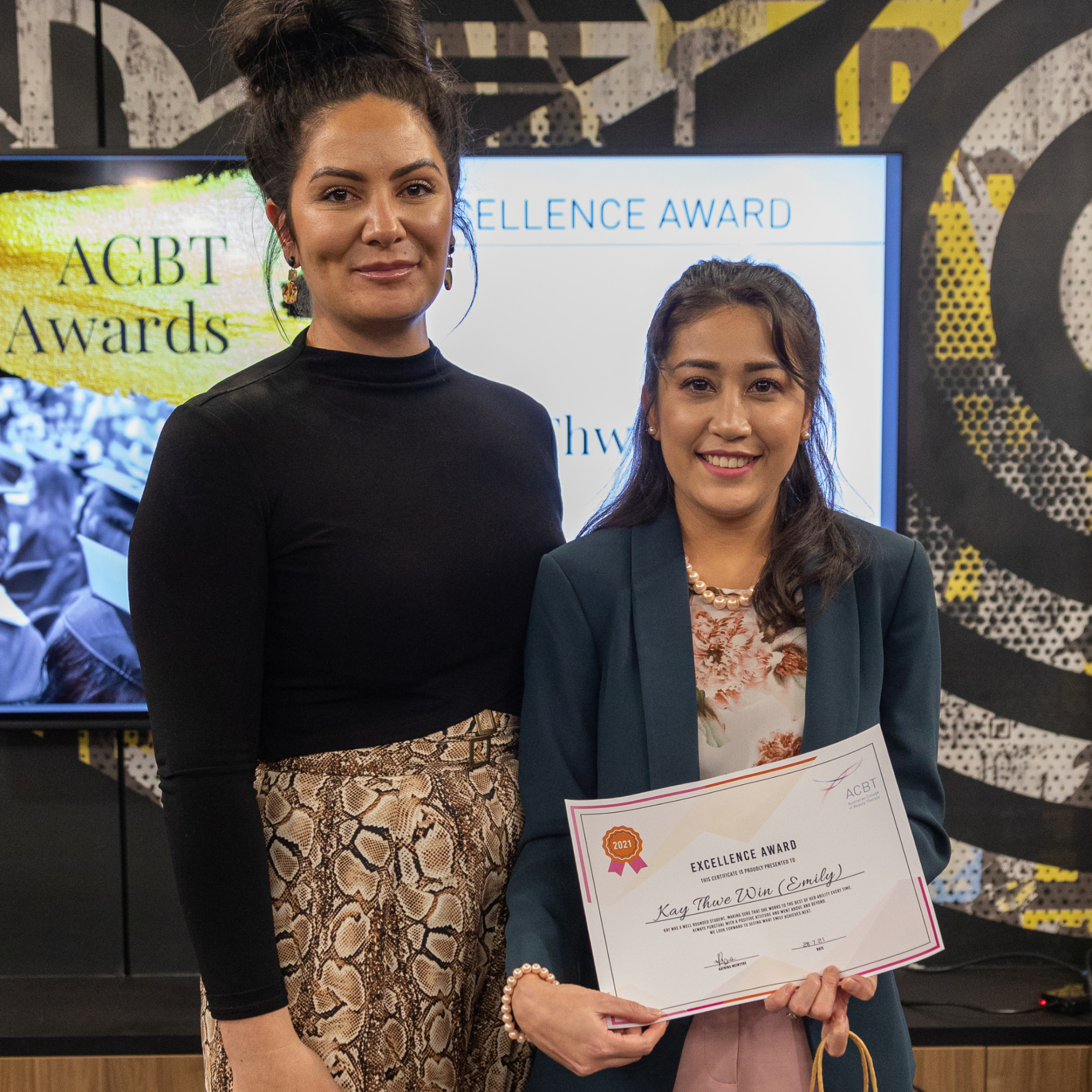 ACBT Graduate, Kay Thwe Win (Emily), accepting her certificate from lecturer, Haylee. Emily is wearing a blue blazer and floral top, and Haylee is wearing a black long sleeved top with pants. Both ladies are smiling.